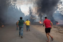 Populares correm durante o incêndio que lavra em Alcabideque , Condeixa-a-Nova