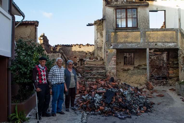 Os três sobreviventes junto à casa destruída pelo fogo. Joaquim Bernardes, com grandes dificuldades de locomoção, e o casal Jorge e Irene