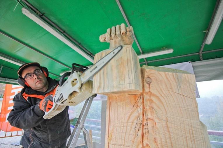 Nelson Ramos está a esculpir figuras em tamanho real com troncos de uma árvore abatida por motivos de segurança