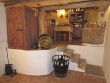 Da sala para a cozinha trepam-se quatro degraus em pedra. Decoração com objetos antigos, como pratos ou alguidares metálicos
