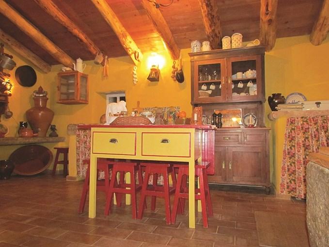 A mesa, de gavetas fundas, pontifica no centro da cozinha rodeada por seis bancos