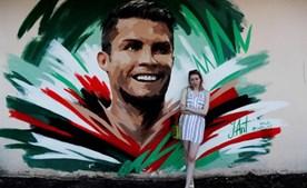 Artista Yulia Antipova ao lado do mural que fez para Ronaldo