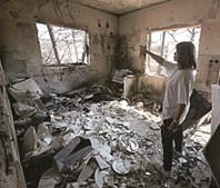 Uma moradora de Mati observa os estragos causados pelo fogo na sua residência