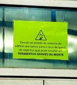 Placa com aviso sobre possível queda de objetos e risco de morte está colocada por cima de uma das entradas do edifício