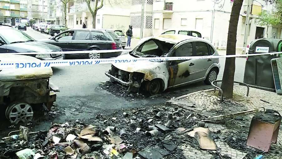 Dois carros parados junto a caixotes do lixo ficaram destruídos pelo fogo no Laranjeiro, Almada