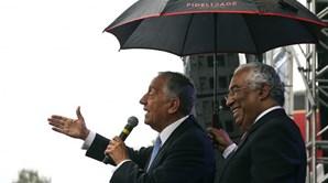Marcelo Rebelo de Sousa e António Costa em Paris. Num discurso à chuva, o primeiro-ministro protege o presidente da república com um guarda-chuva. Marcelo comenta: 'Estão a ver o que é a colaboração entre os dois poderes?'.