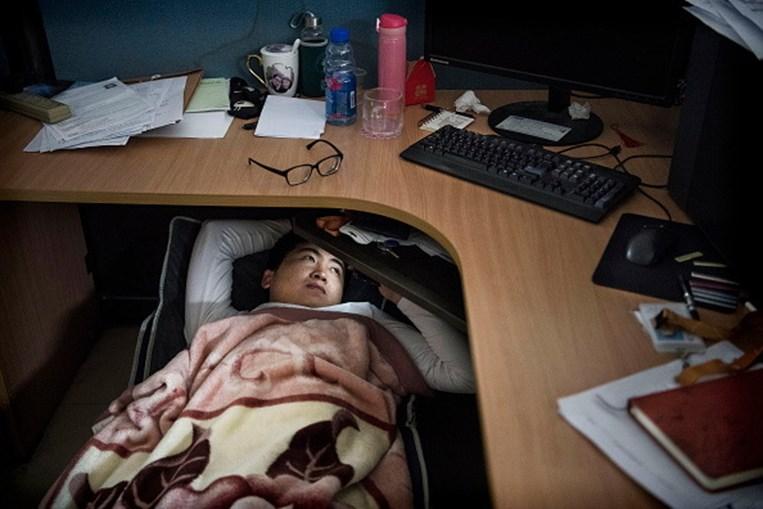 Trabalhador da Huawei descansa debaixo da secretária
