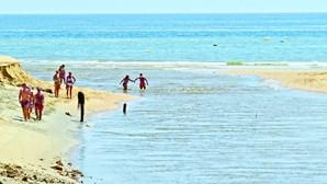 Praia dos Salgados com água escura e suja