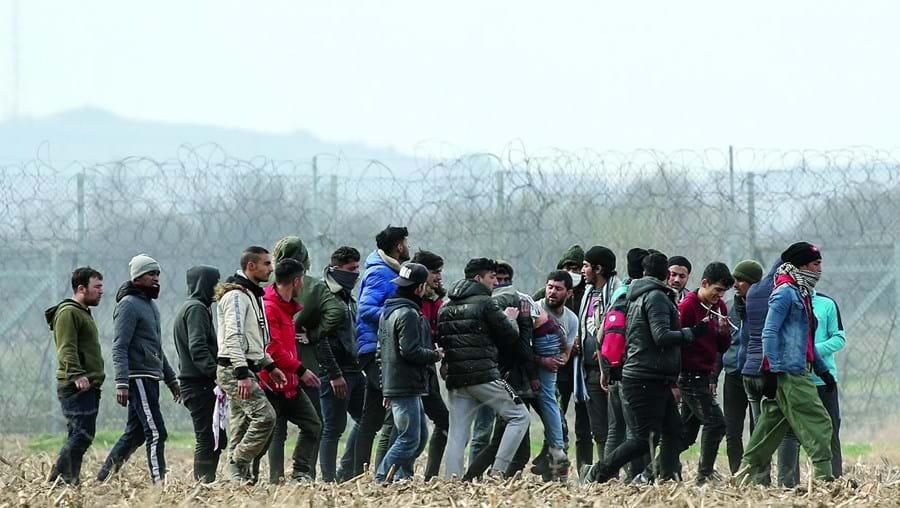 Refugiados transportam uma pessoa ferida nos confrontos junto à fronteira grega, onde foram recebidos com gás lacrimogéneo e canhões de água