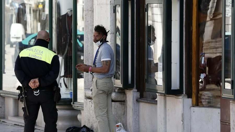 Um agente Polícia Municipal junto de um sem-abrigo que tem máscara.