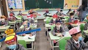 Crianças chinesas utilizam chapéus de um metro para manter distância social na escola