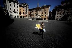 Mulher caminha com compras no centro de Roma, Itália, abril de 2020