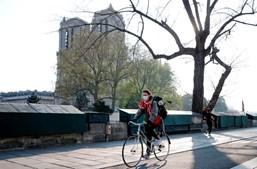 Mulher anda de bicicleta com máscara em Paris, França, abril de 2020
