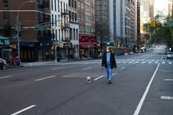 Um médico passeia o cão nas ruas de Manhattan em Nova Iorque, EUA