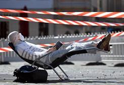 Homem protegido com máscara e óculos apanha apanha sol enquanto lê um livro durante pandemia em Dresden, na Alemanha