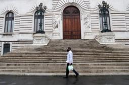 Homem caminha nas ruas desertas de Roma, abril 2020