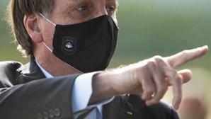 Apoiantes de Jair Bolsonaro com máscaras e tochas em manifestação contra Supremo Tribunal Federal
