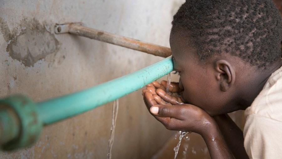Criança bebe água numa escola em África
