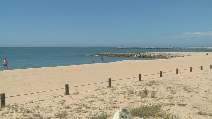 Areal da praia de Quarteira quase vazio em dia de calor. População aproveita paredão para caminhar