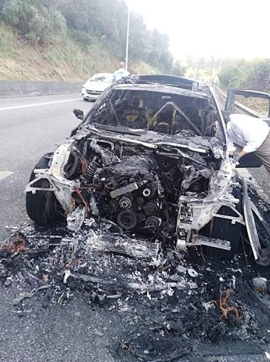 Carro consumido pelas chamas em Lisboa no acesso à ponte 25 de Abril, sentido Norte-Sul