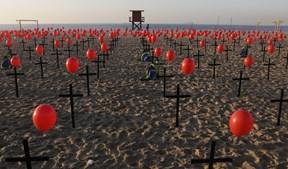 Cruzes negras na praia de Copacabana homenageiam as 100 mil vítimas mortais do coronavírus no Brasil