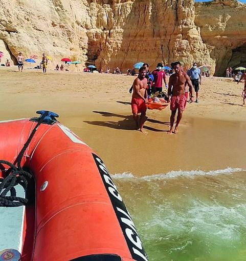 Banhista parte pernas a mergulhar de rocha em praia de Lagoa