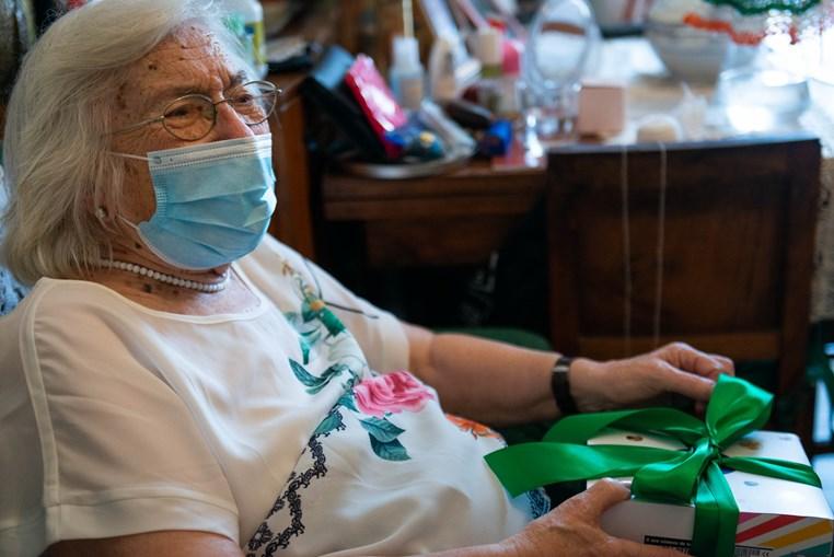 Dona Fernanda Barbosa a receber um smartphone em casa para poder passar a ver os rostos de amigos e familiares