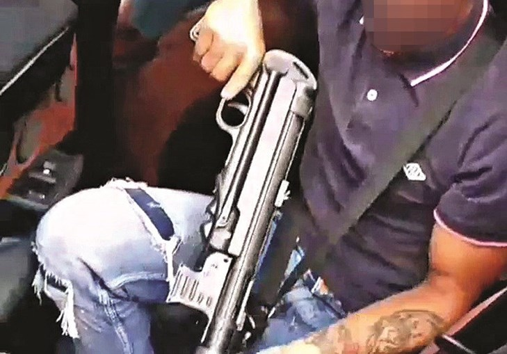 Homem surge sentado num carro a exibir a arma. Autoridades investigam suspeitos que surgem num vídeo