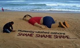 O artista indiano Sudarsan Pattnaik trabalha em uma escultura de areia que representa o menino sírio Alan Kurdi