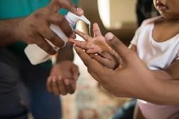 Criança lava as mãos com gel desinfetante