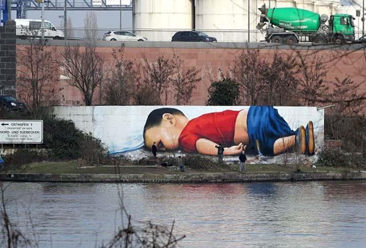 Um graffiti dos artistas Justus Becker e Oguz Sen retrata o menino refugiado sírio Alan Kurdi