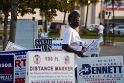 Uma apoiante do Partido Democrata com cartazes de apelo ao voto
