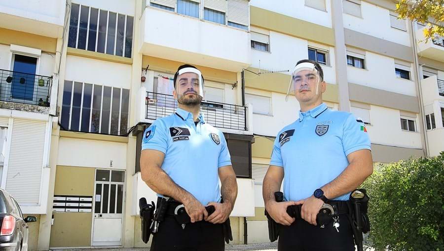 Agentes André Ferreira (à esquerda) e João Costa junto ao prédio onde salvaram, ao colo, os idosos