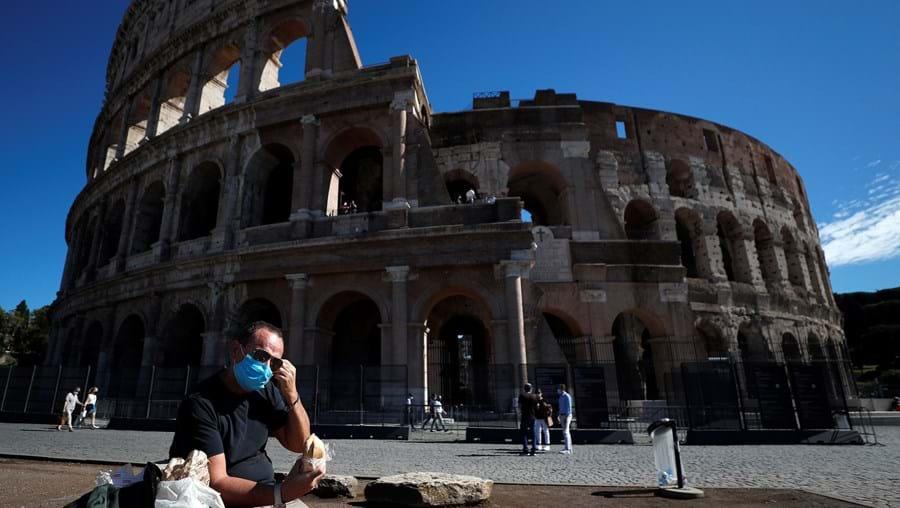 Homem com máscara descansa num banco junto ao Coliseu de Roma, em Itália