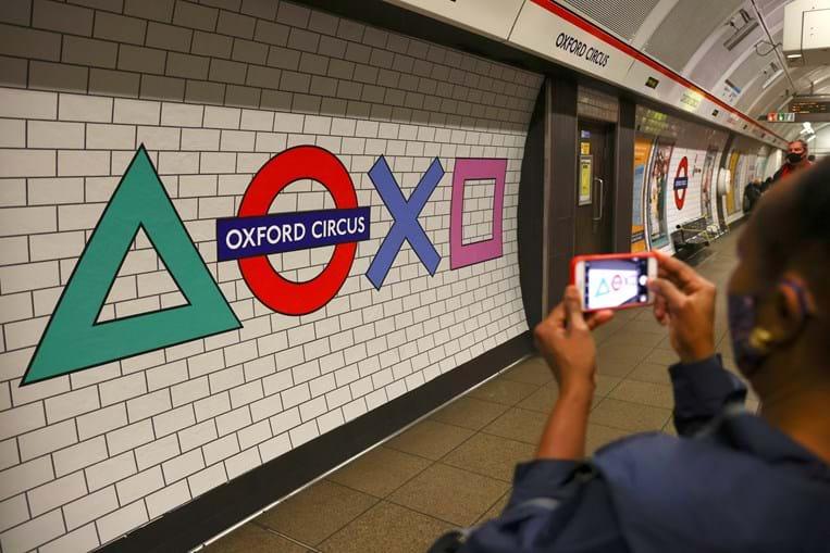 Passageiros fotografam simbologia do comando da Playstation colocada nas paredes do metro da estação de metro de Oxford Circus, em Londres