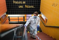 Assistente desinfeta corrimões das escadas