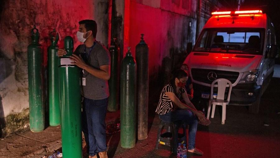 Homem agarra garrafa de oxigénio, em Manaus