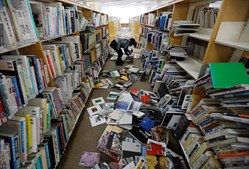 Membros de uma livraria apanham e arrumam livros que caíram de estantes após sismo