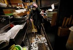 Mitsue Hisa, 70 anos, proprietária de um bar, limpa os destroços
