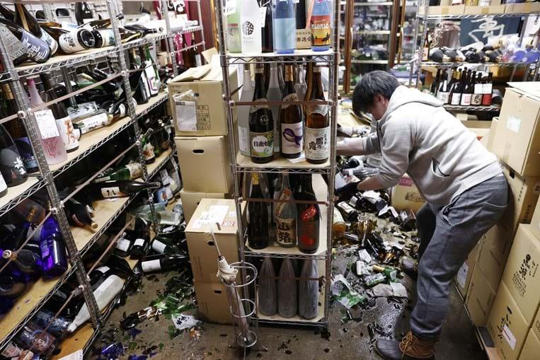Trabalhadores limpam e arrumar garrafas numa loja após o abalo