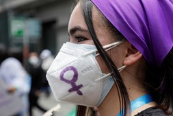 Mulher usa máscara cirúrgica com o símbolo feminino num protesto para marcar o Dia Internacional da Mulher em La Paz, na Bolívia
