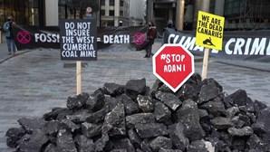 Ativistas pelo clima despejam carvão falso em frente ao mercado de seguros Lloyd's of London