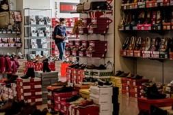 Uma funcionária da Sapataria Bruna arruma o espaço comercial, na baixa de Faro, 15 de abril de 2021. O comércio local na baixa de Faro procura resistir às restrições impostas pelo combate à pandemia de covid-19