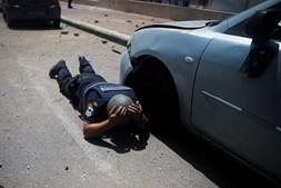 Agente da polícia israelita protege-se ao ouvir alarmes de raides aéreos