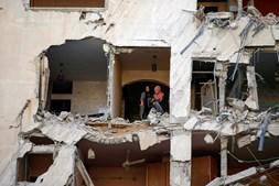 Mulheres palestinianas inspecionam o edifício onde habitavam após destruição causada por ataques israelitas