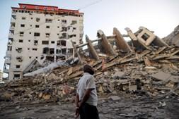 Homem palestiniano observa destruição causada por ataques aéreos israelitas