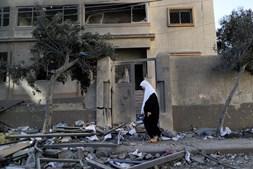 Mulher palestiniana caminha nos destroços de edifícios colapsados