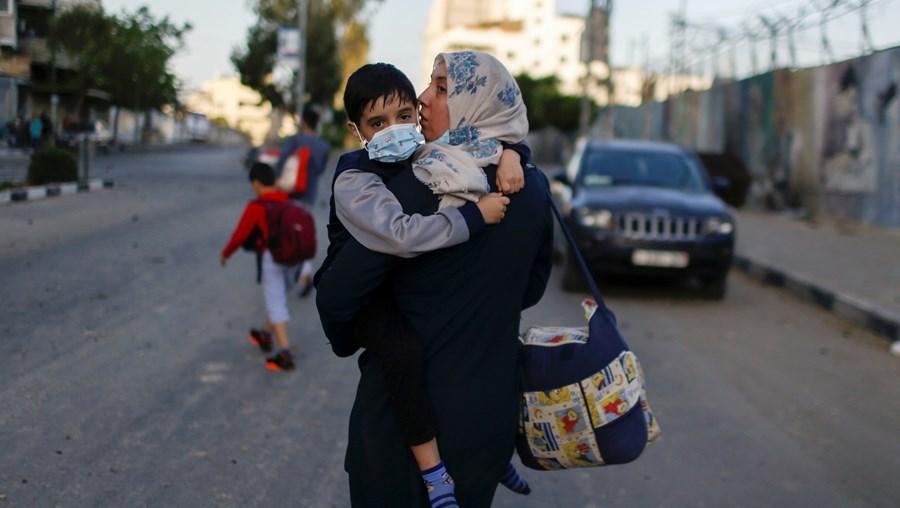 Mulher palestiniana caminha com o filho ao colo após abandonar a sua casa devido a ataque israelita