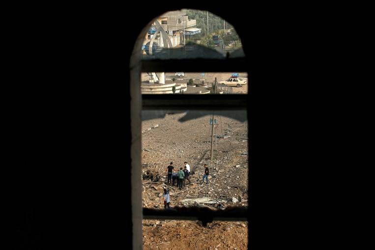 Palestinianos analisam local após ataque aéreo israelita