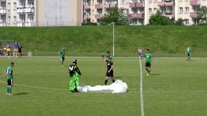 Paraquedista aterra no meio de jogo de futebol